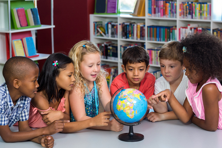 multi ethnic children: Multi ethnic children looking at globe on table in library