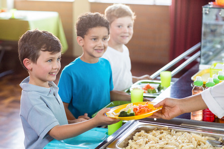 Cropped image of woman serving food to smiling schoolchildren in canteen Stock Photo