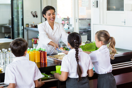 Woman serving food to children in school canteen