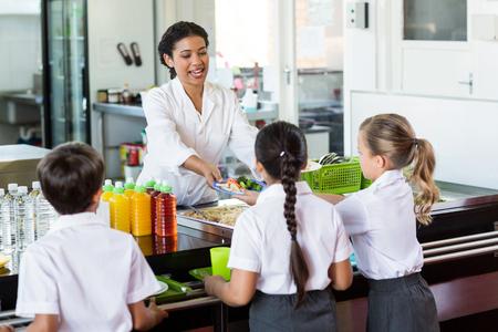 comedor escolar: La mujer que sirve comida a los niños en el comedor escolar