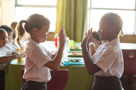 comedor escolar: Girls playing clapping game in school canteen Foto de archivo