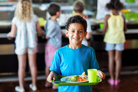 food tray: Portrait of happy schoolboy holding food tray in canteen against classmates