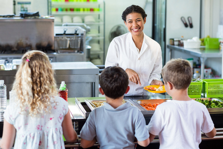 Cheerful woman serving food to schoolchildren in canteen