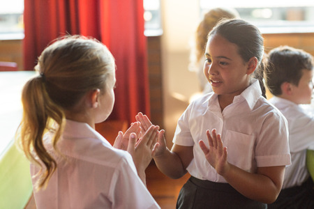 school canteen: chicas lindas que juegan al juego que aplaude en el comedor escolar Foto de archivo