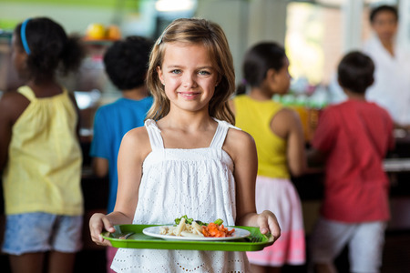 Portrait of cute schoolgirl holding tray in canteen against classmates