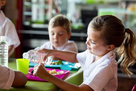 comedor escolar: Colegiala sonriente vertiendo agua en vidrio de consumición en la cantina