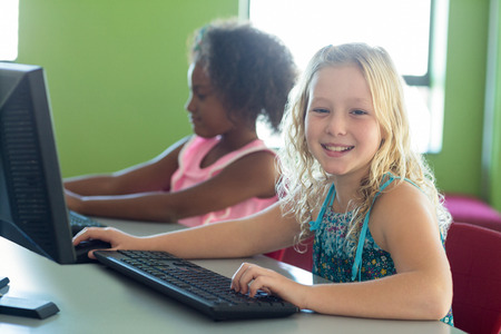 classmate: Portrait of happy girl with classmate using computers in classroom