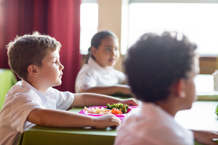 school canteen: El muchacho lindo con sus compañeros de comedor escolar