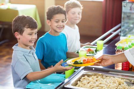 料理を食堂の小学生に女性のトリミングされた画像 写真素材