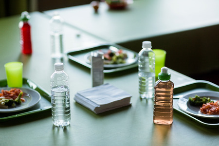 school canteen: Vista de ángulo alto de la comida con las botellas de agua en la mesa de comedor escolar Foto de archivo