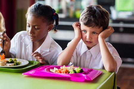 school canteen: niño reflexivo linda con compañeros de clase en comedor escolar