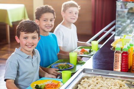 school canteen: Retrato de la sonrisa de los escolares de pie cerca del mostrador de comedor escolar Foto de archivo