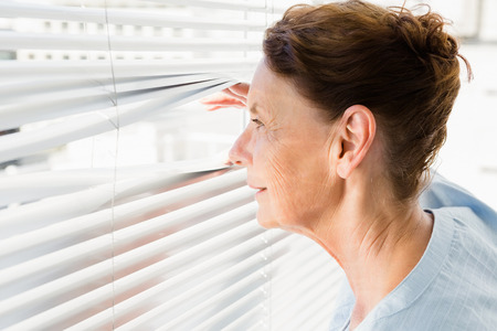 inquiring: Close-up of mature woman looking through blinds