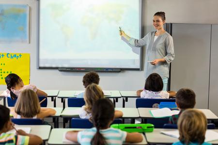 Femeninos escolares enseñanza del profesor utilizando la pantalla del proyector en el aula