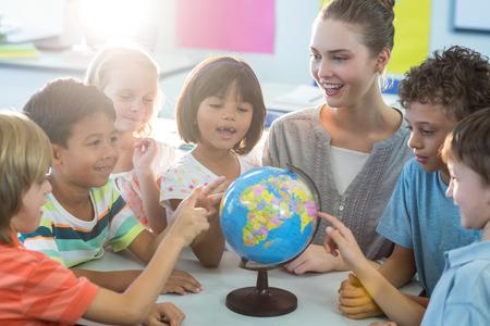 笑顔の女教師が教室の小学生に地球を表示