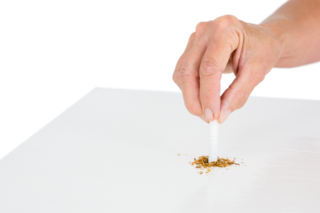 bad habit: Cropped image of person holding broken cigarette at table against white background