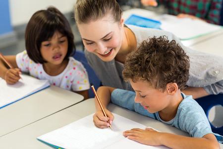 educator: Happy female teacher helping schoolchildren to write on book