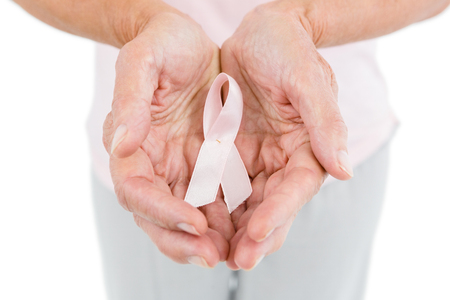 cropped out: Midsection of woman showing anti-violence ribbon while standing against white background Stock Photo