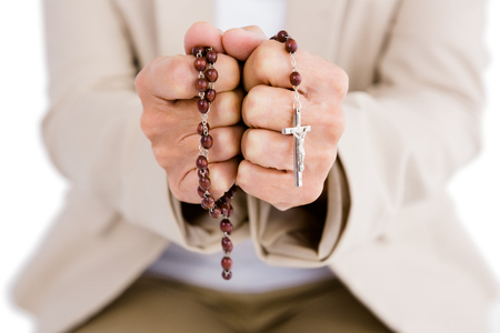 a beads: Midsection of woman holding rosary beads