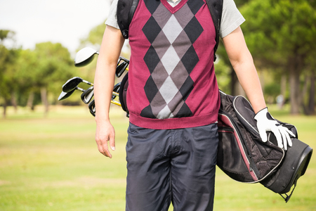 golf bag: Midsection of man wearing golf bag while standing on field Stock Photo