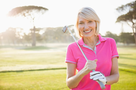 woman golf: Woman posing with her golf club on field