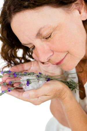 sensory perception: Smiling mature woman smelling flowers while standing at spa