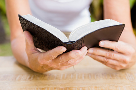 bible reading: Midsection of woman reading bible at table Stock Photo