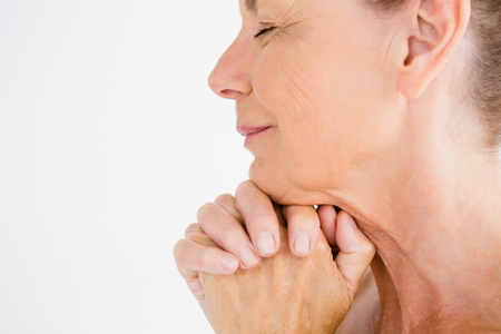 Cropped image of mature woman praying against white background