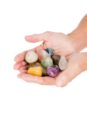 cropped: Cropped image of person holding colorful pebbles against white background Stock Photo