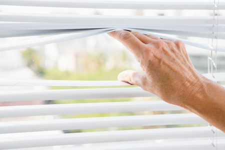 personal perspective: Cropped image of person hand on blinds