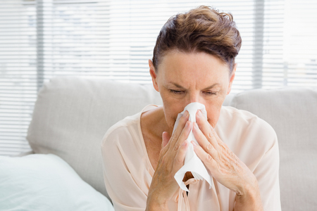 blowing nose: Mature woman with blowing nose while sitting on sofa at home