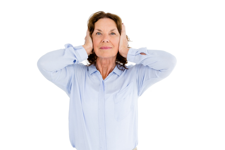 hands covering ears: Portrait of smiling woman with hands covering ears against white background