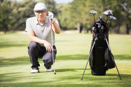 crouching: Golfer crouching and posing on field Stock Photo