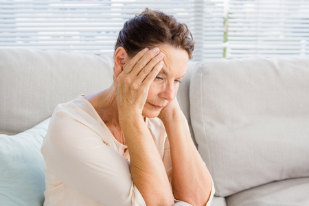 Woman with head in hands while sitting on sofa at home Stock Photo