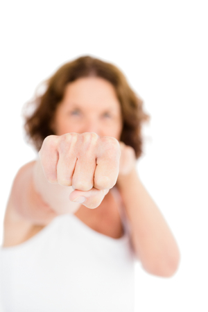 punched out: Portrait of woman punching while standing against white background
