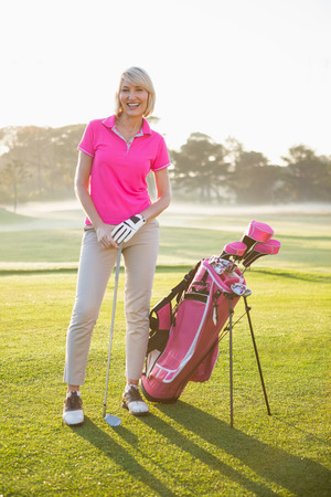 woman golf: Woman golfer posing with her golf equipments on field