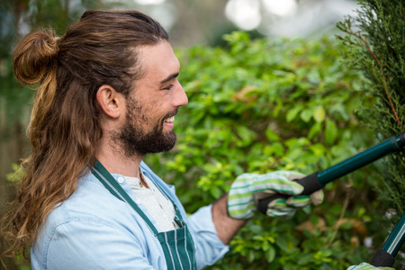 clippers: Happy young male gardener using hedge clippers at communicty garden
