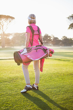 golf bag: Rear view of sportswoman holding a golf bag on a field