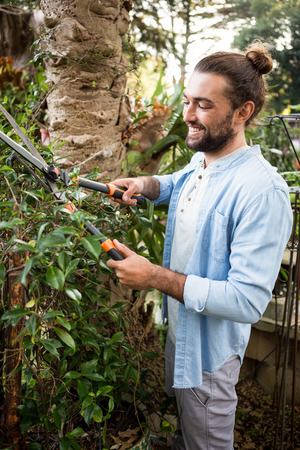 community garden: Happy young worker using hedge clippers at community garden Stock Photo