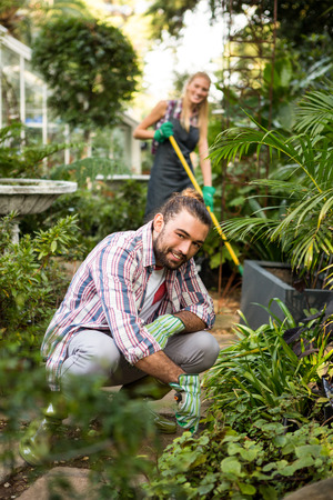 garden staff: Portrait of happy young male gardener with colleague in community garden Stock Photo