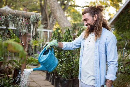 regar las plantas: Feliz joven jardinero de las plantas de riego de sexo masculino en jardín de la comunidad Foto de archivo