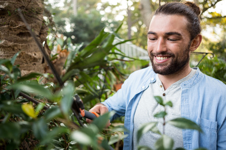 clippers: Happy confident young male gardener using hedge clippers at garden