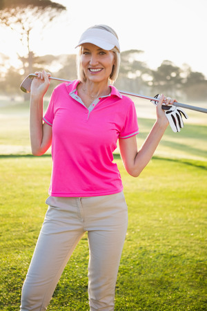 woman golf: Woman golfer posing with her golf club on field