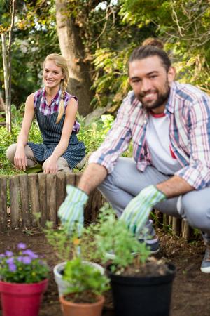 crouching: Portrait of happy young gardeners crouching at botanical garden Stock Photo