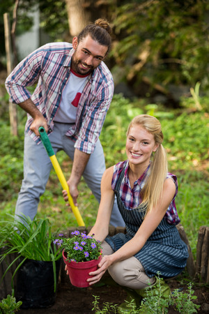 garden staff: Portrait of happy young gardeners with potted plant and shovel at botanical garden