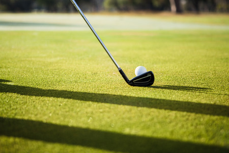pursuits: Close up of a golf ball and club on field