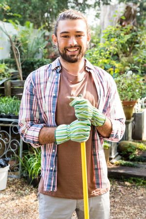 community garden: Portrait of young hipster gardener with tool at community garden Stock Photo