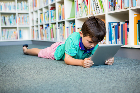 Boy using digital tablet while lying in school library Imagens