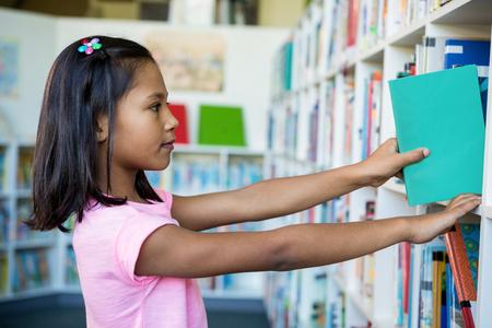 Girl searching books on bookshelves in school library