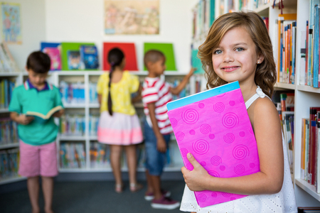Portrait of smiling girl holding books in school library Imagens